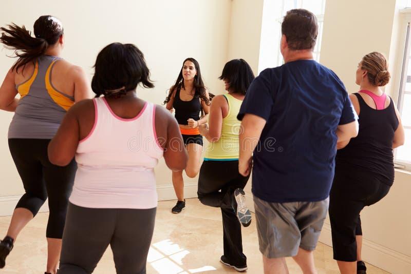 Инструктор фитнеса в классе тренировки для полных людей стоковое фото rf