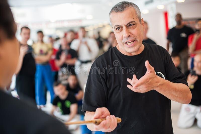 Инструктор Avi Nardia Kapap демонстрирует нож воюя его студентов стоковая фотография