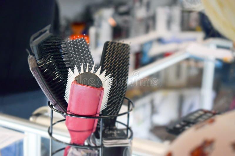 Инструменты волос, различные щетки волос, гребни, Piks в стойке на магазине салона стоковая фотография rf