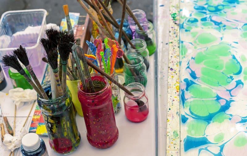 Инструменты для рисовать на воде в методе ebru Установка красок на воду с последующей передачей приводя картины стоковые изображения