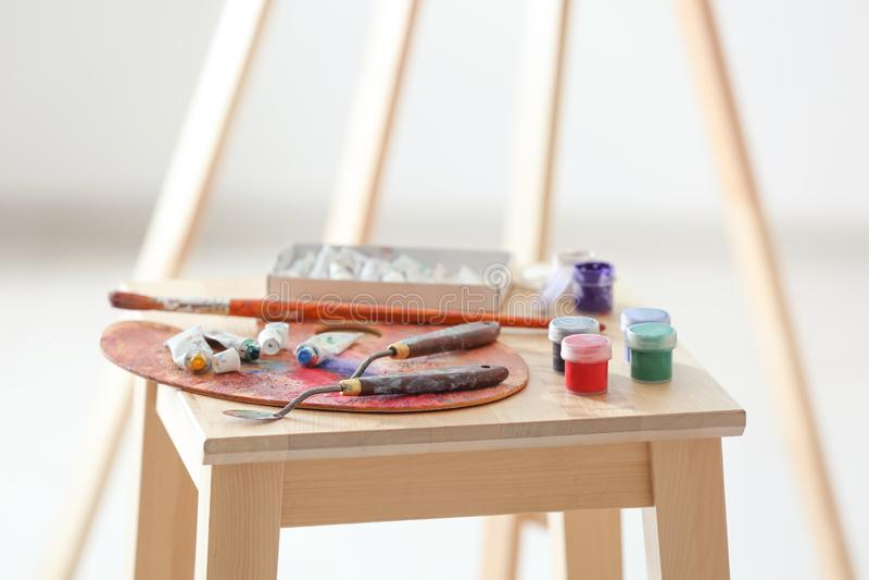Инструменты и краски профессионального художника на деревянном стуле стоковое фото rf