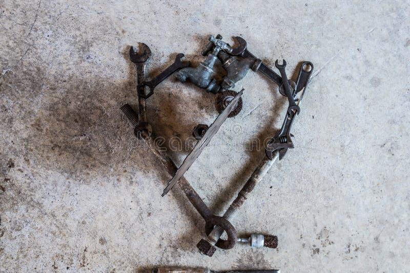 Инструменты и части аранжировали в сломленном сердце влюбленности на цементе стоковое изображение
