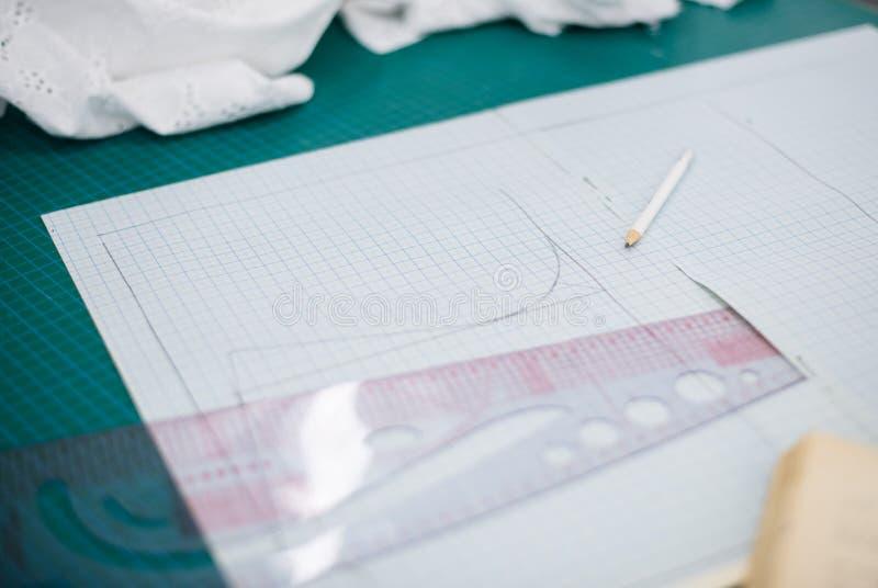 Инструменты, картины и образцы ткани на шить таблице в мастерской портноя стоковые фотографии rf