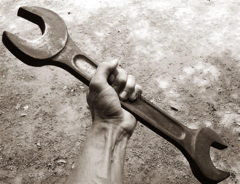 Инструмент гаечного ключа владением руки механика в руке стоковые изображения rf