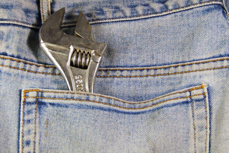 Инструмент ключа в голубых карманных джинсах стоковая фотография rf
