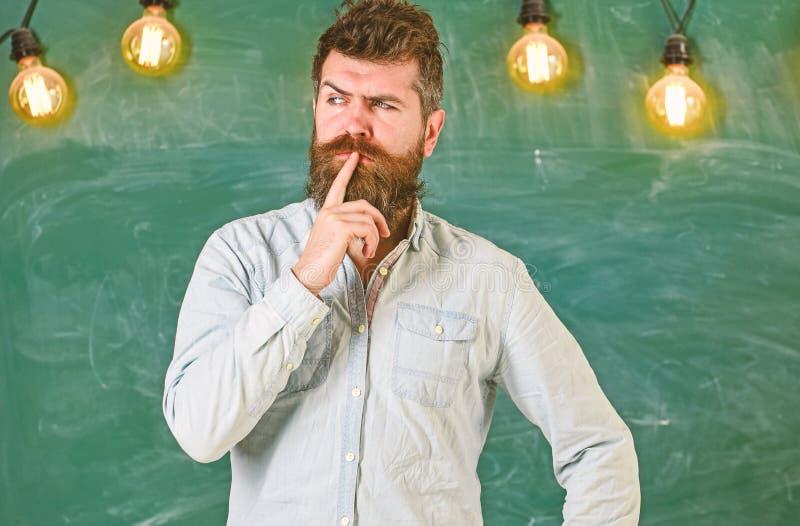 Интеллектуальная концепция задачи Бородатый битник в рубашке, доске на предпосылке Гай думая с заботливым выражением стоковая фотография rf
