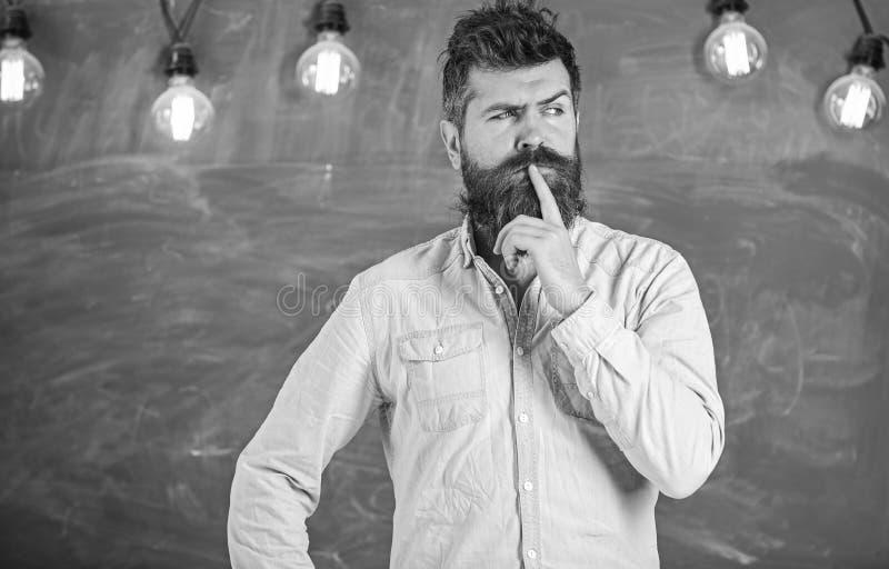 Интеллектуальная концепция задачи Человек с бородой и усик на внимательной стойке стороны перед доской Мысль Гай стоковое фото