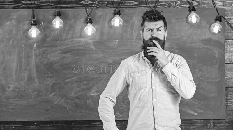 Интеллектуальная концепция задачи Человек с бородой и усик на внимательной стойке стороны перед доской Бородатый хипстер стоковая фотография rf