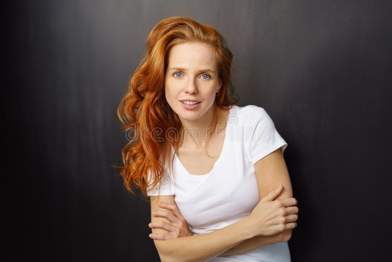 Интенсивная молодая женщина с симпатичными длинными красными волосами стоковые изображения rf