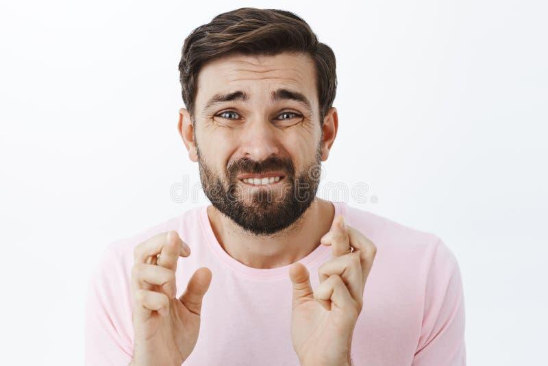 Интенсивный надеющийся парень в скорбе гримасничая в прошении, сдерживая губе и хмурясь перекрестный палец для удачи как молить стоковые фото