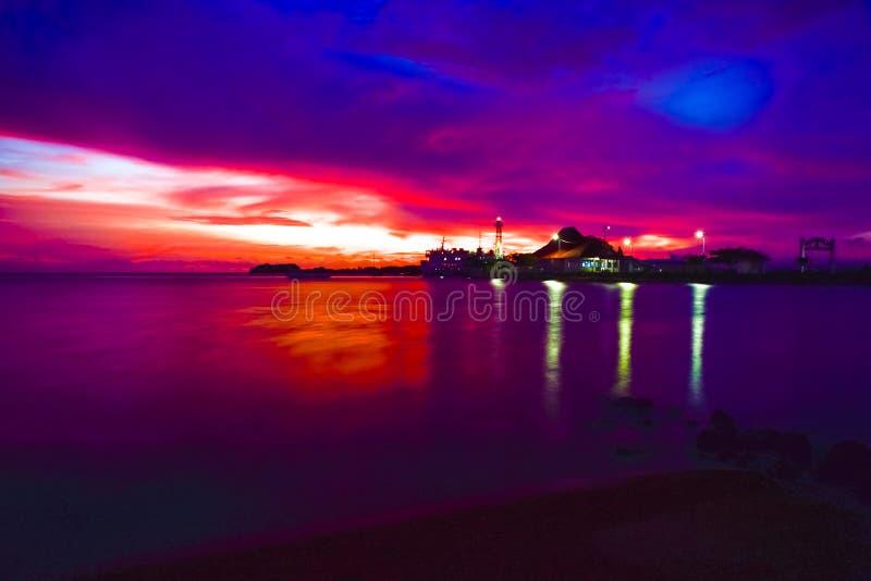 Интенсивный оранжевый заход солнца на удаленном изолированном тропическом пляже стоковое изображение
