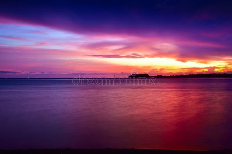 Интенсивный оранжевый заход солнца на удаленном изолированном тропическом пляже стоковая фотография
