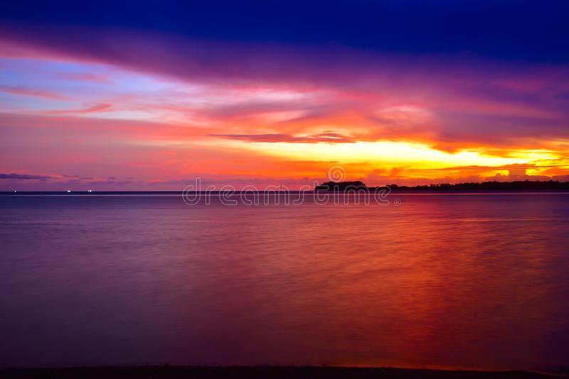 Интенсивный оранжевый заход солнца на удаленном изолированном тропическом пляже стоковая фотография rf