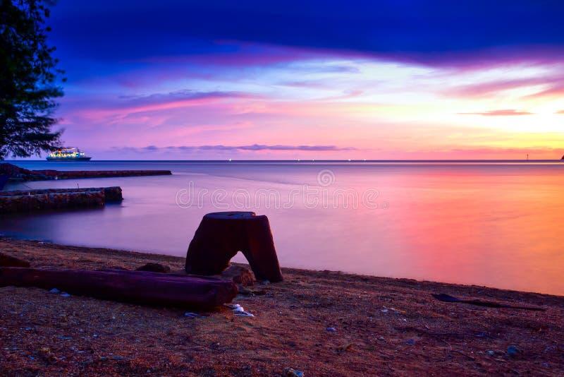 Интенсивный оранжевый заход солнца на удаленном изолированном тропическом пляже стоковые изображения rf