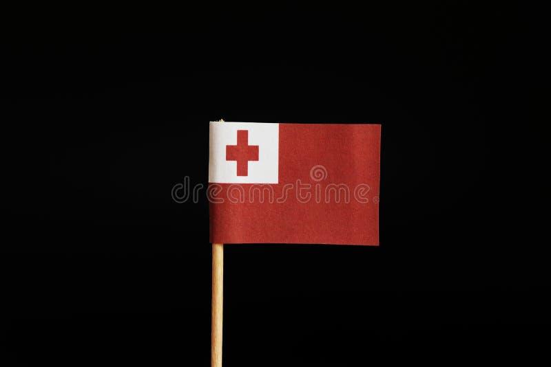 Интересный флаг Тонги на деревянной ручке на черной предпосылке Тонга принадлежит к Океании стоковая фотография