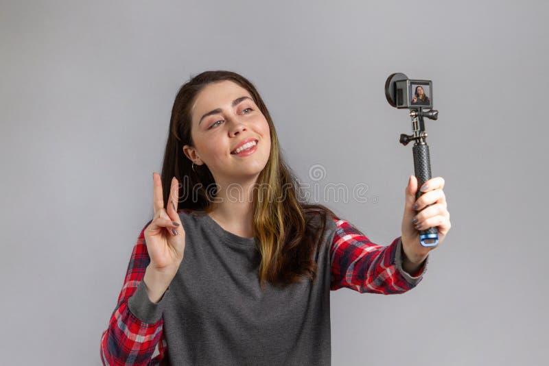 Интернет и ведение блогов Молодая женщина позирует для селфи на портативной мини-камере стоковые изображения rf