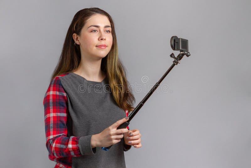 Интернет и ведение блогов Молодая женщина снимается на портативной мини-камере стоковое фото rf