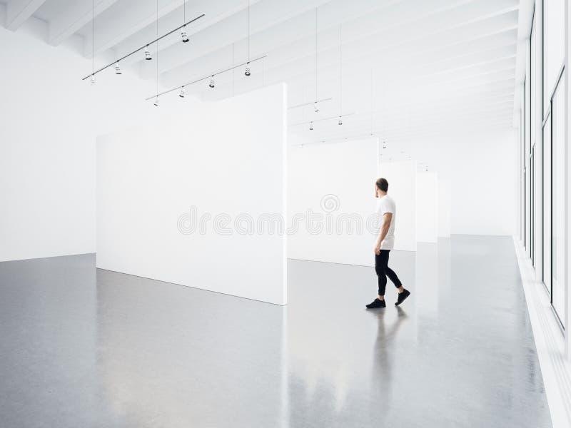Интерьер галереи с белым холстом и молодым человеком стоковое изображение rf