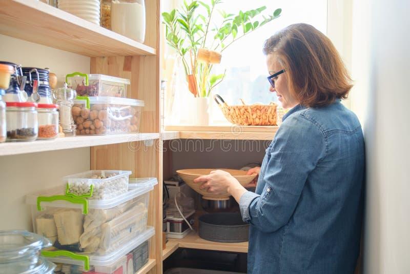Интерьер деревянной кладовки с продуктами для варить Взрослая женщина принимая kitchenware и еду от полок стоковое изображение rf