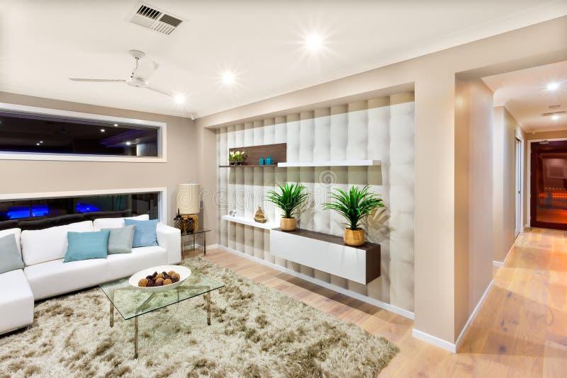 Интерьер живущей комнаты в роскошном доме со светами дальше стоковые фото