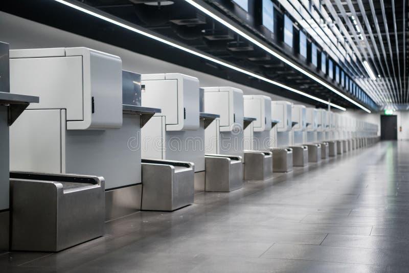 Интерьер зоны регистрации в современном авиапорте: багаж признавает стержни при багаж регулируя системы ленточного транспортера стоковое фото rf