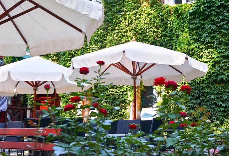 Интерьер кафа улицы лета с белым зонтиком в зеленом парке города, богато украшенном с цветками и декоративными элементами стоковая фотография rf