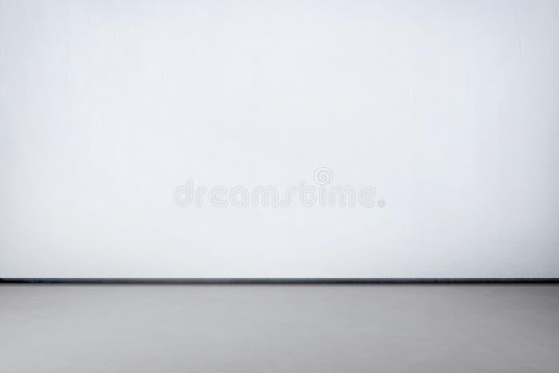 Интерьер комнаты с белой стеной и конкретным серым полом стоковая фотография