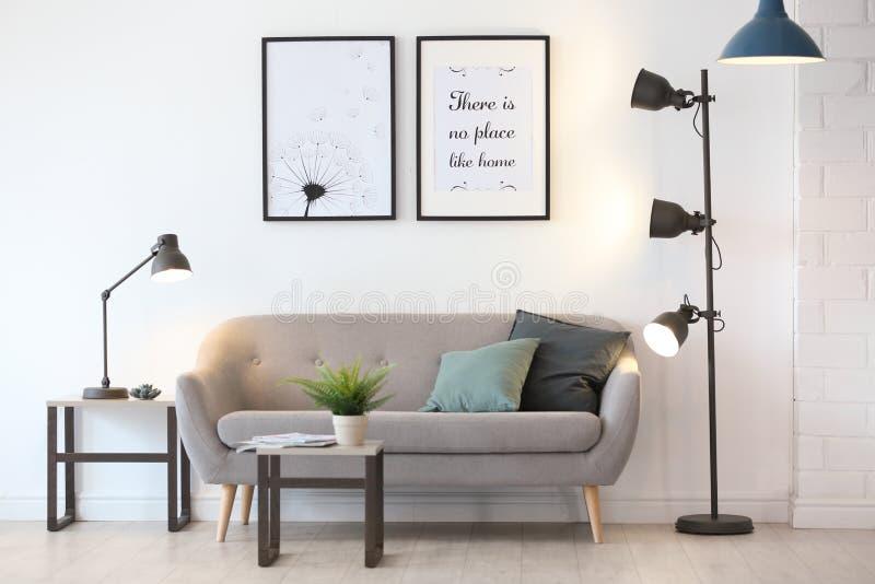 Интерьер комнаты с современными лампами и софой стоковые фото