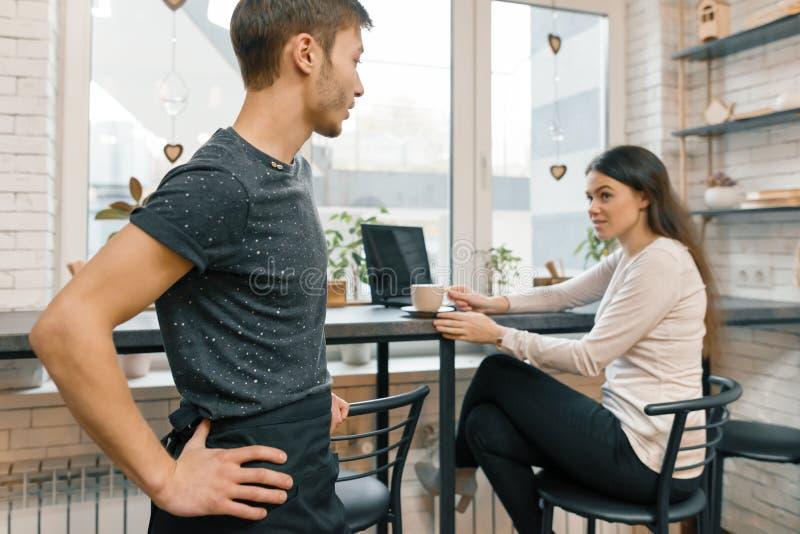 Интерьер кофейни, молодой женщины разговаривая с работником кафа с чашкой кофе на таблице стоковая фотография