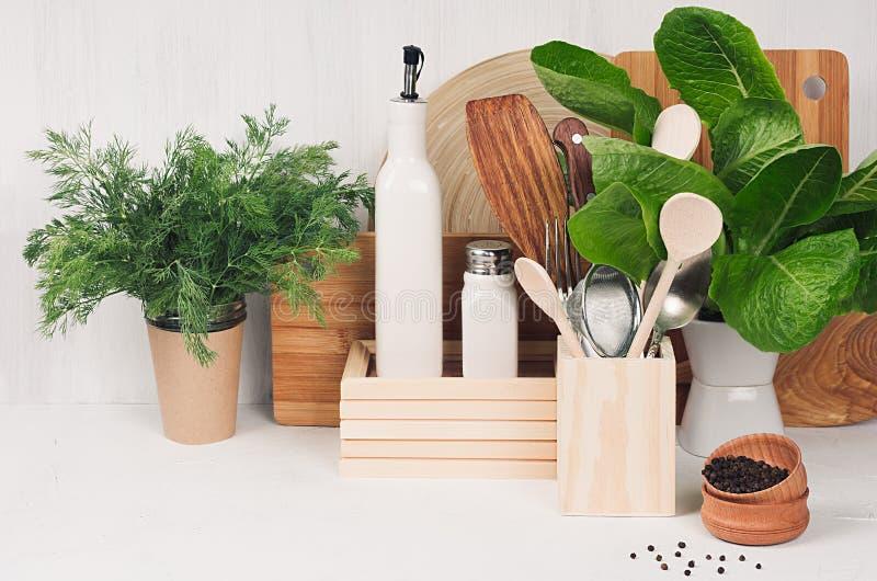Интерьер кухни белый с деревянным бежевым kitchenware, специями, керамикой и зеленым кустом шпината на светлой деревянной доске,  стоковые фотографии rf