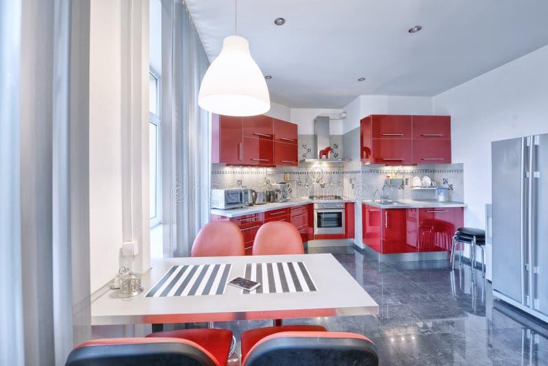 Интерьер кухни в доме красного цвета современном стоковое изображение