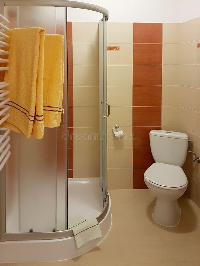 Интерьер небольшого bathroom в мягких и теплых бежевых цветах Размещение ливня и туалета в туалете бюджета Гигиена тела стоковые изображения