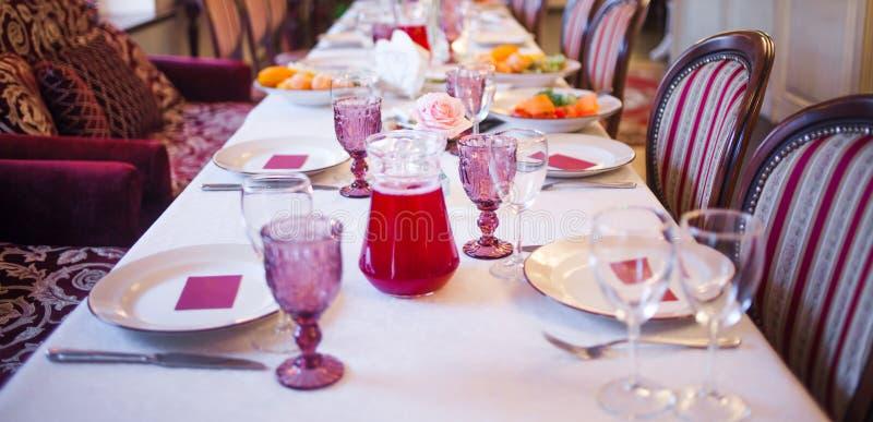 Интерьер ресторана, большая таблица клал для банкета, украшенный в бургундских тонах стоковая фотография