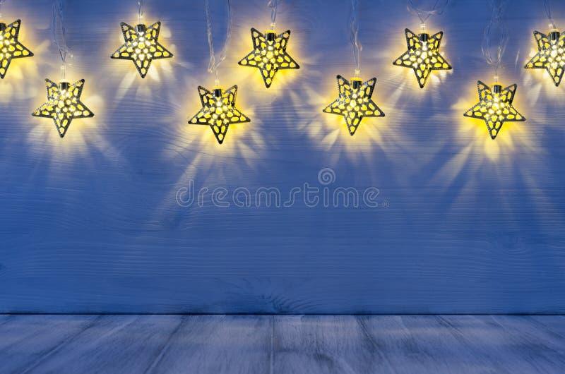 Интерьер рождества пустой с заревом освещает желтые звезды на предпосылке древесины сини индиго стоковое фото rf