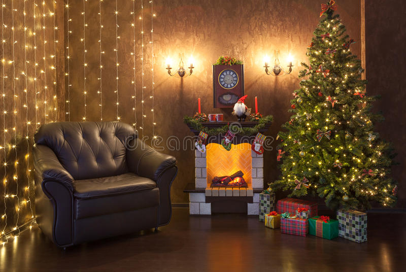 Интерьер рождества дома в вечере Рождественская елка украшенная с светами, огонь горит в камине стоковые фото