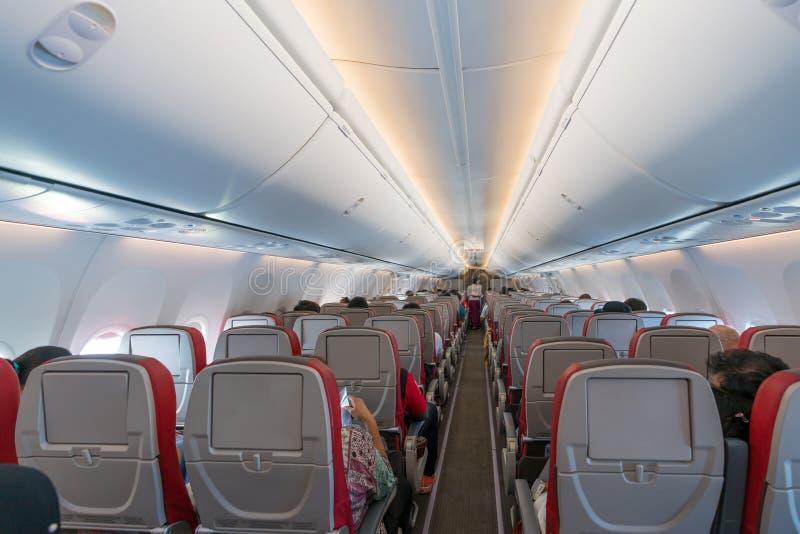 Интерьер самолета с пассажирами на местах и stewardess внутри стоковое изображение rf