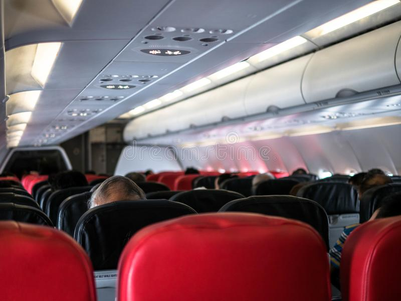 Интерьер самолета Air Asia с пассажирами сидя на местах стоковые фото