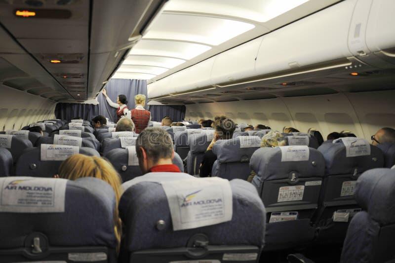 Интерьер самолета airmoldova с пассажирами на местах и stewardess идя проход стоковые фото