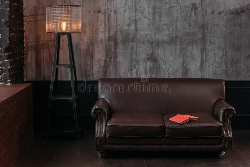 интерьер стильной комнаты в дизайне просторной квартиры при книга лежа на кресле стоковые изображения