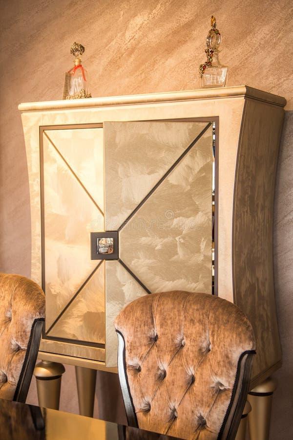 Интерьер части роскошный Золотые шкафчик и стулья стоковое фото