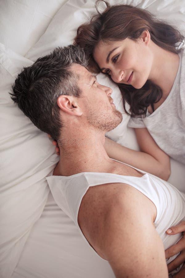 Интимные молодые пары лежа в кровати стоковое фото rf