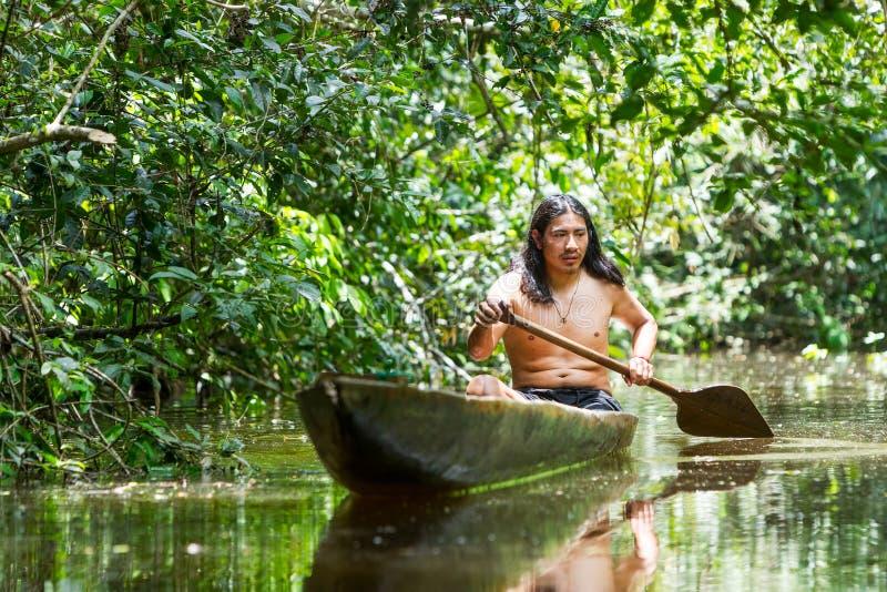 Индигенный взрослый человек в деревянном каное стоковая фотография rf