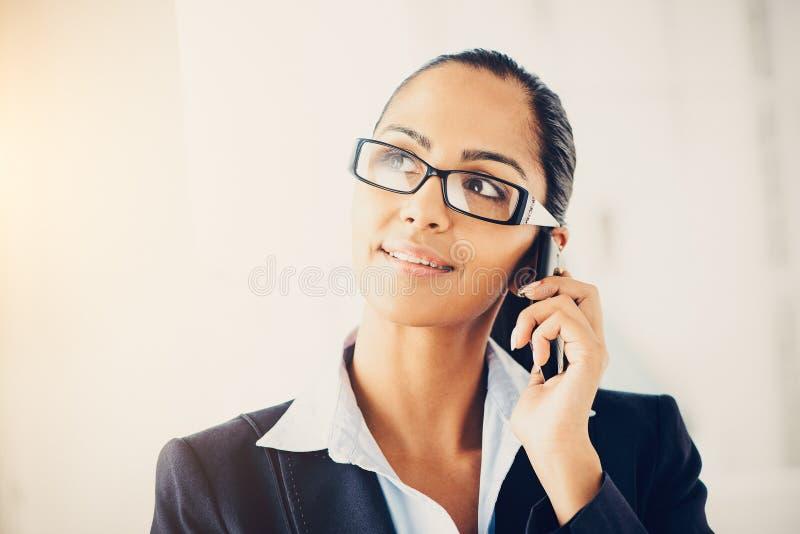 Индийская бизнес-леди используя мобильный телефон счастливый стоковое фото