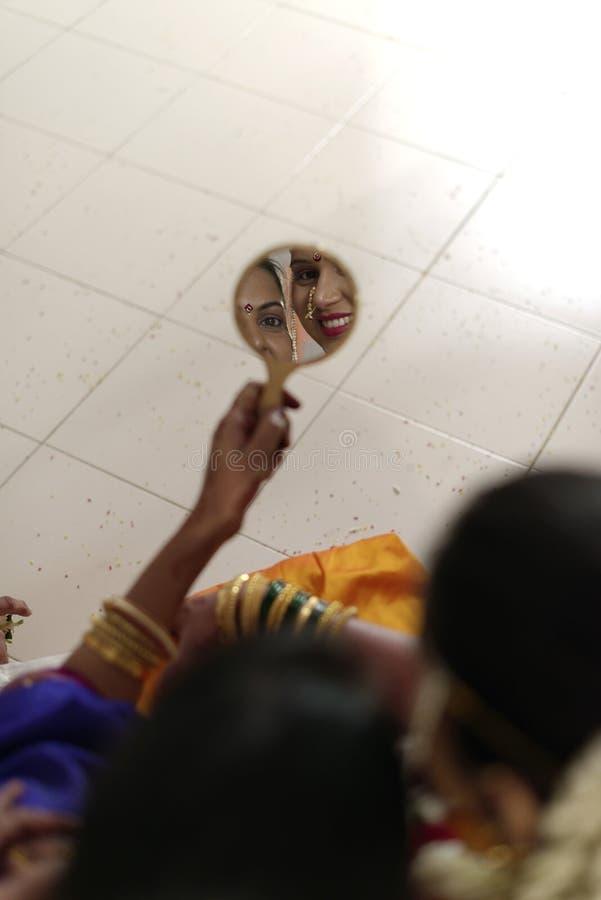 Индийская индусская невеста при ее теща смотря в зеркале в свадьбе махарастры стоковые изображения