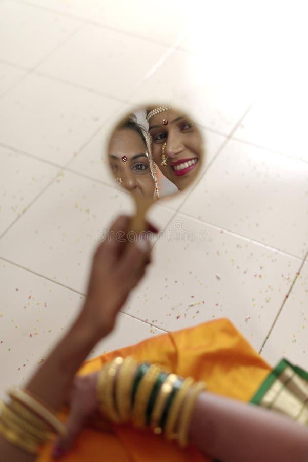Индийская индусская невеста при ее теща смотря в зеркале в свадьбе махарастры стоковая фотография