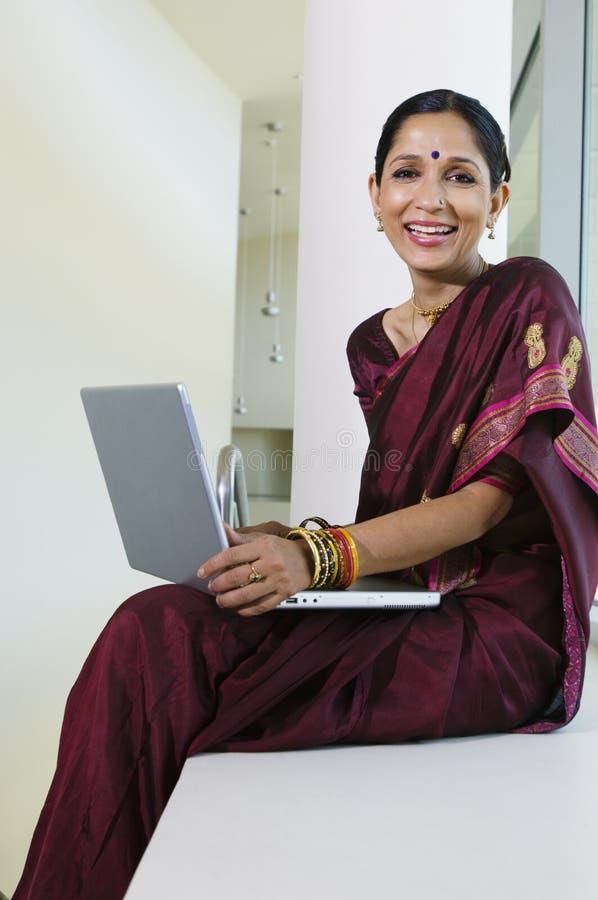 Индийская коммерсантка работая на компьтер-книжке стоковая фотография
