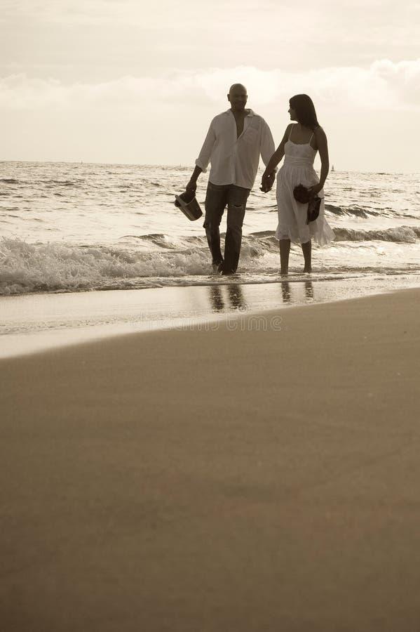 Индийские пары держа руки идя на пляж совместно стоковое изображение rf