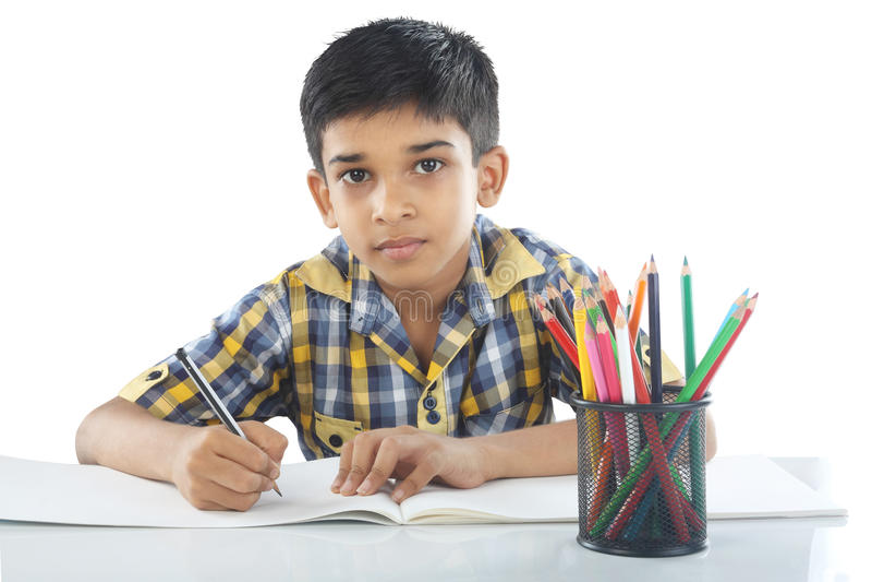 Индийский мальчик с примечанием и карандашем чертежа стоковые изображения