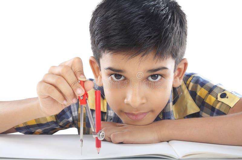 Индийский мальчик с примечанием и карандашем чертежа стоковая фотография rf