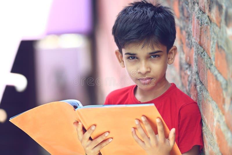 Индийский мальчик с учебником стоковая фотография rf